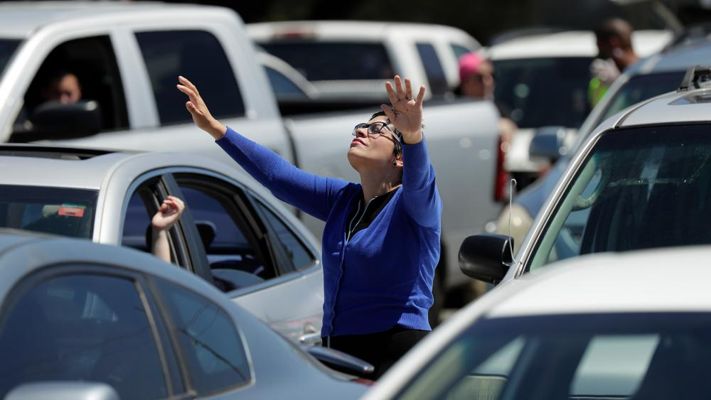 A church goer stands by her car as she worships in the parking lot in San Antonio, April 12, 2020. (AP Photo/Eric Gay)