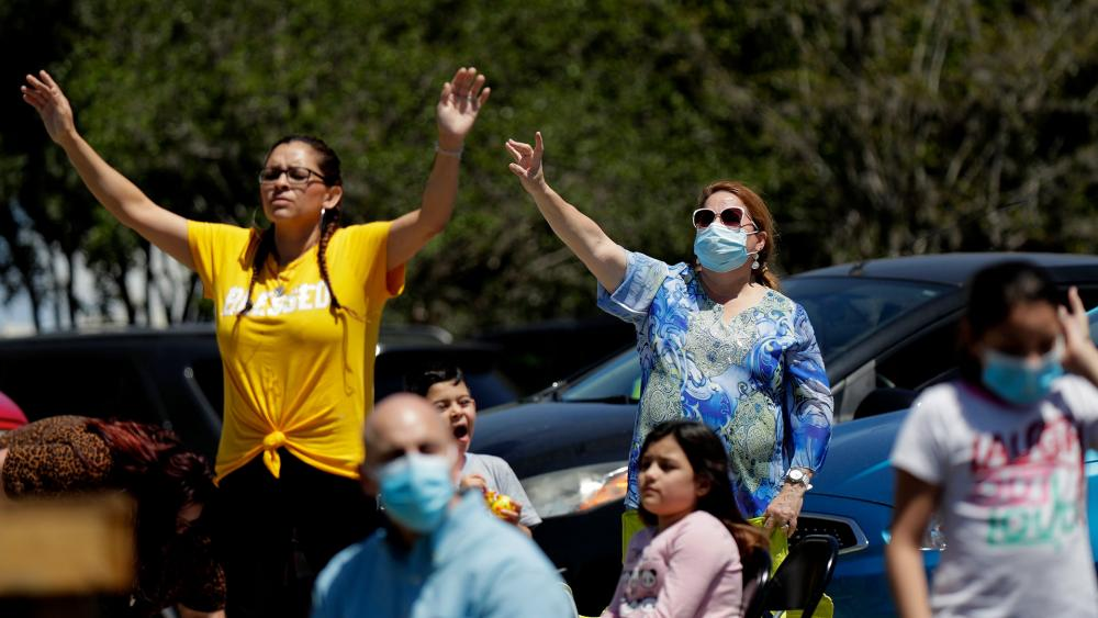 Churchgoers attend service in the parking lot of Xtreme Harvest Church in San Antonio, TX (AP Photo/Eric Gay)