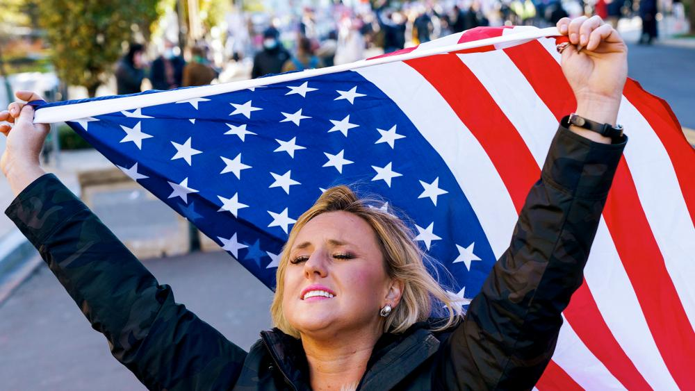 With the White House in the background, Kelly Janowiak of Chicago, prays with a conservative Christian Evangelical group while holding a American flag, Nov. 2, 2020 (AP Photo/Jacquelyn Martin)