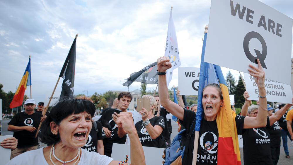 Supporters of QAnon shout slogans against the government's measures to prevent the spread of COVID-19 infections during a rally on Aug. 10 (AP Photo/Vadim Ghirda)
