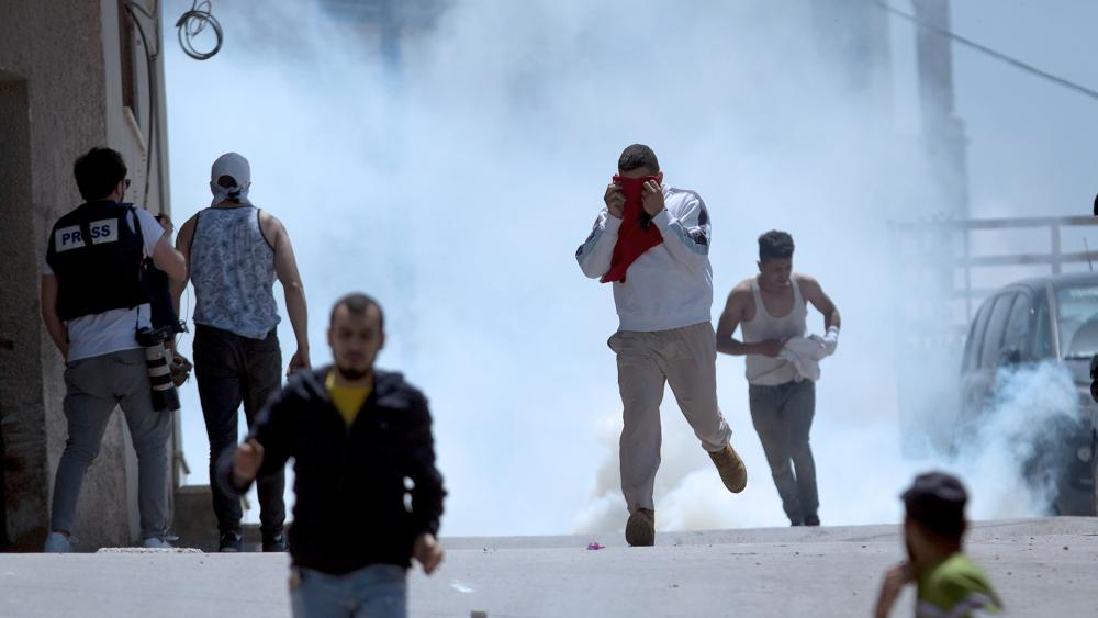 AP Photo: Palestinians run away from tear gas fired by Israeli soldiers during clashes after a soldier was killed