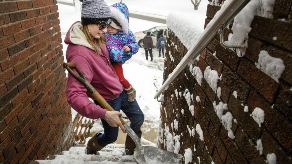 Morgan Miller carries her one-year-old daughter Mia Jennings in one arm as she shovels the stairs to her Springfield home with the other on Sunday, Jan. 13. AP Photo.