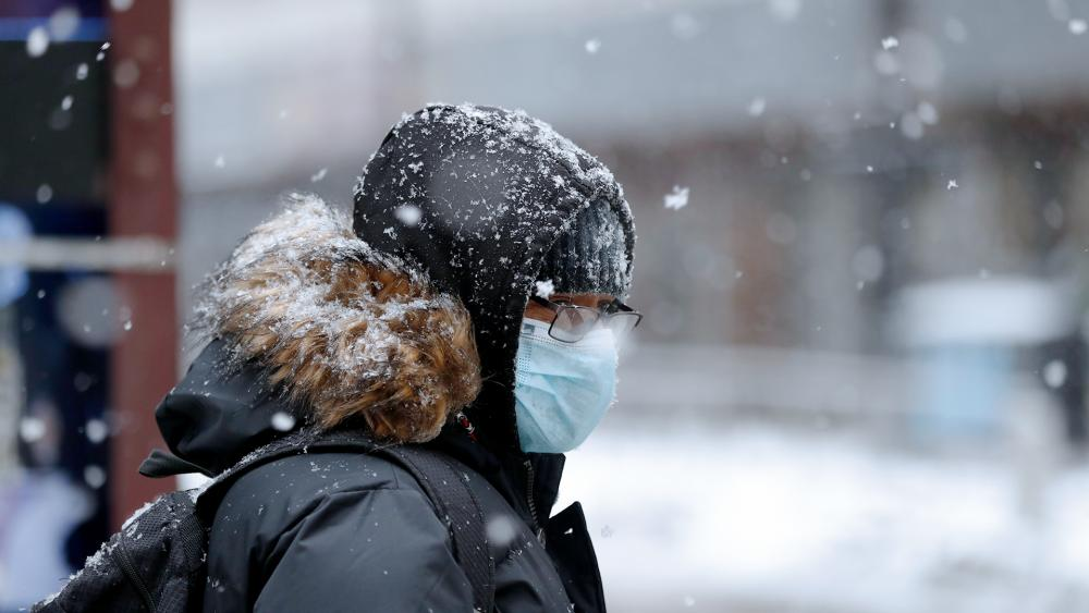 A person is seen covered with snow during a snowstorm in Chicago on Monday, Feb. 8, 2021. (AP Photo/Shafkat Anowar)