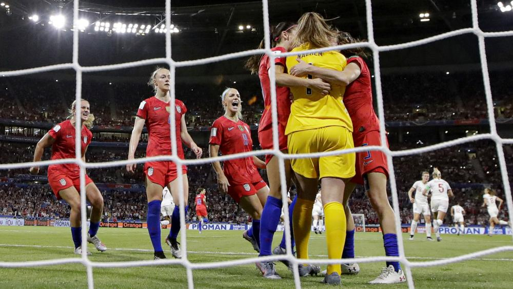 Team mates hug United States goalkeeper Alyssa Naeher after she saved a penalty shot taken by England's Steph Houghton during the Women's World Cup semifinal soccer match between England and the United States.  (AP Photo/Alessandra Tarantino)
