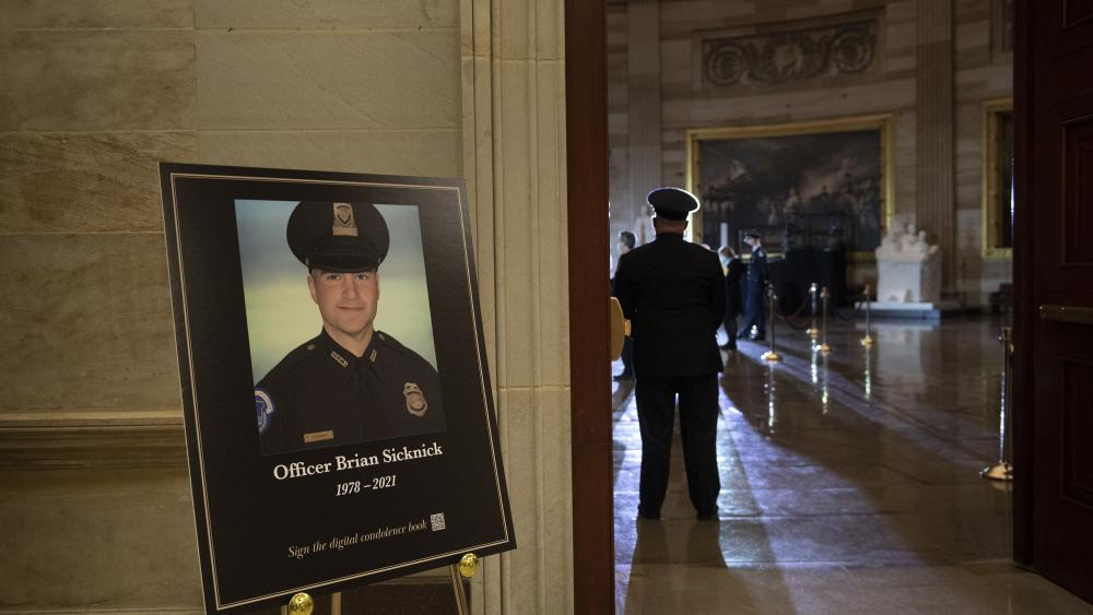 FILE - In this Feb. 2, 2021, file photo a placard is displayed with an image of the late U.S. Capitol Police officer Brian Sicknick.  (Brendan Smialowski/Pool via AP, File)