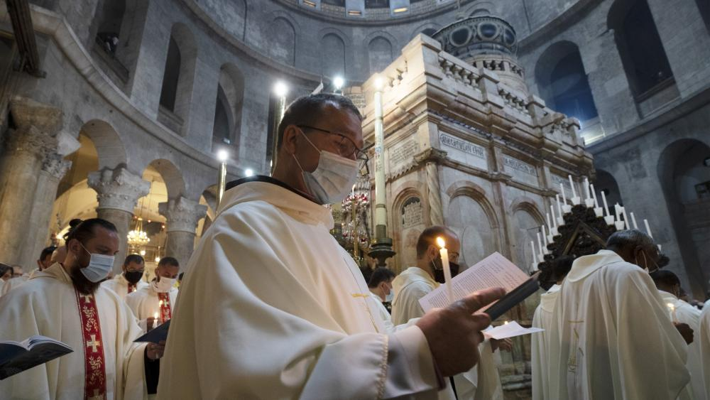 Priests circle the Holy Sepulchre during Holy Thursday mass led by the Latin Patriarch in the Old City of Jerusalem, Thursday, April 1, 2021. (AP Photo/Maya Alleruzzo)