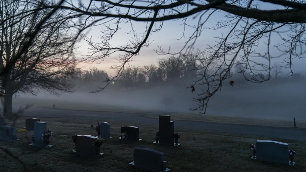 In this Wednesday, March 17, 2021 file photo, morning fog blankets a cemetery in West Virginia. (AP Photo/David Goldman)