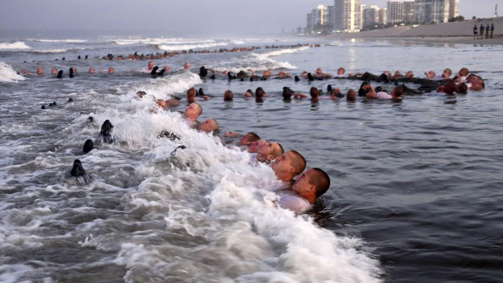"""This May 4, 2020, photo provided by the U.S. Navy shows SEAL candidates participating in """"surf immersion"""" during Basic Underwater Demolition/SEAL (BUD/S) training. (MC1 Anthony Walker/U.S. Navy via AP)"""