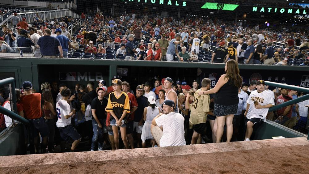 Spectators stand in the visiting team dugout during a stoppage in play due to an incident near the ballpark in the sixth inning of a baseball game between the Washington Nationals and the San Diego Padres, Saturday, July 17, 2021, in Washington.(AP Photo)