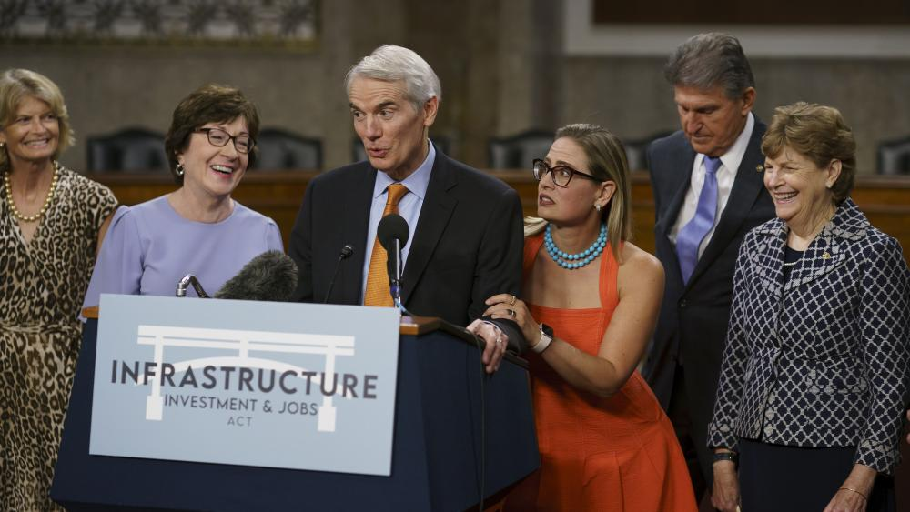 The bipartisan group of Senate negotiators speak to reporters just after a vote to start work on a nearly $1 trillion bipartisan infrastructure package, at the Capitol in Washington, Wednesday, July 28, 2021. (AP Photo/J. Scott Applewhite)