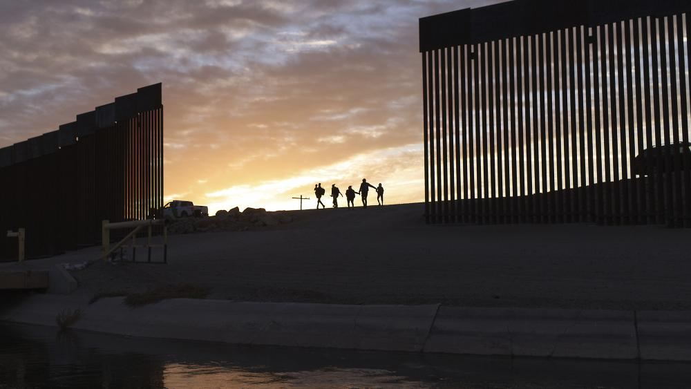 In this Thursday, June 10, 2021, file photo, a pair of migrant families from Brazil pass through a gap in the border wall to reach the United States after crossing from Mexico to Yuma, Ariz., to seek asylum. AP Photo