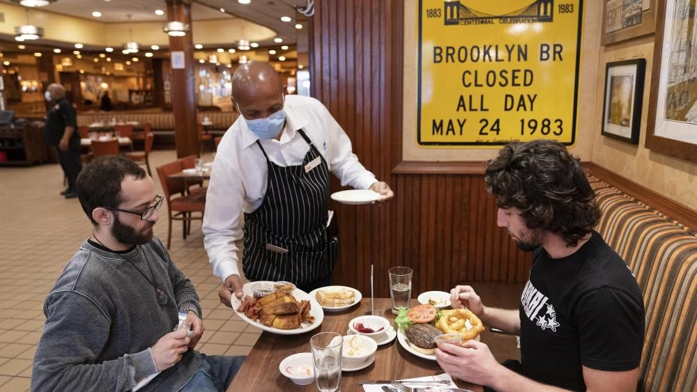 FILE - In this Sept. 30, 2020, file photo, Waiter Lenworth Thompson serves lunch to David Zennario, left, and Alex Ecklin at Junior's Restaurant in New York. (AP Photo/Mark Lennihan, File)