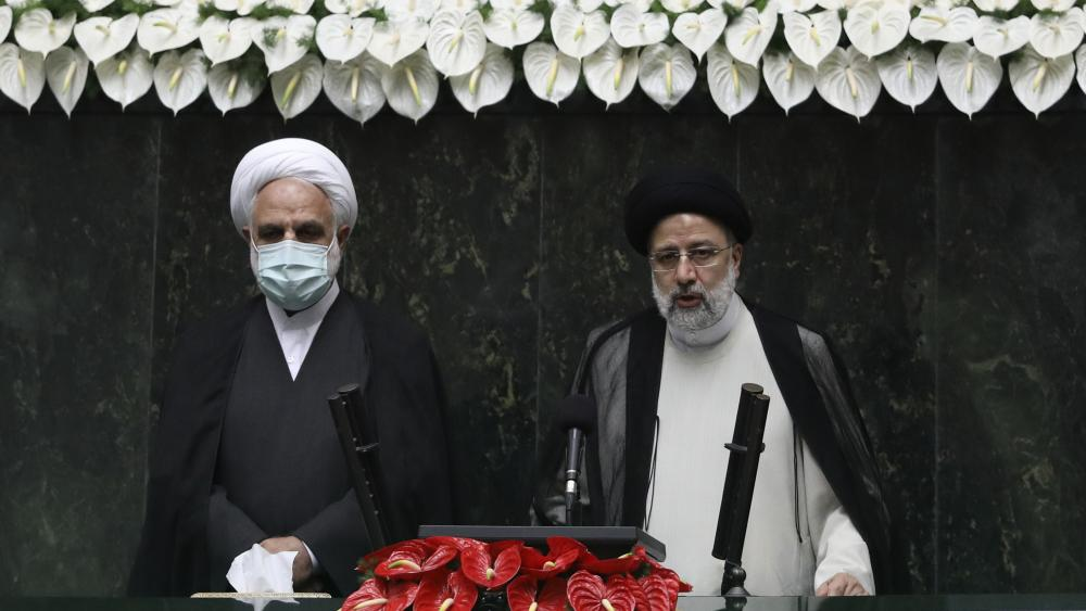President Ebrahim Raisi, right, takes his oath as president, as Judiciary Chief Gholamhossein Mohseni Ejehi listens in a ceremony at the parliament in Tehran, Iran, Thursday, Aug. 5, 2021. (AP Photo/Vahid Salemi)