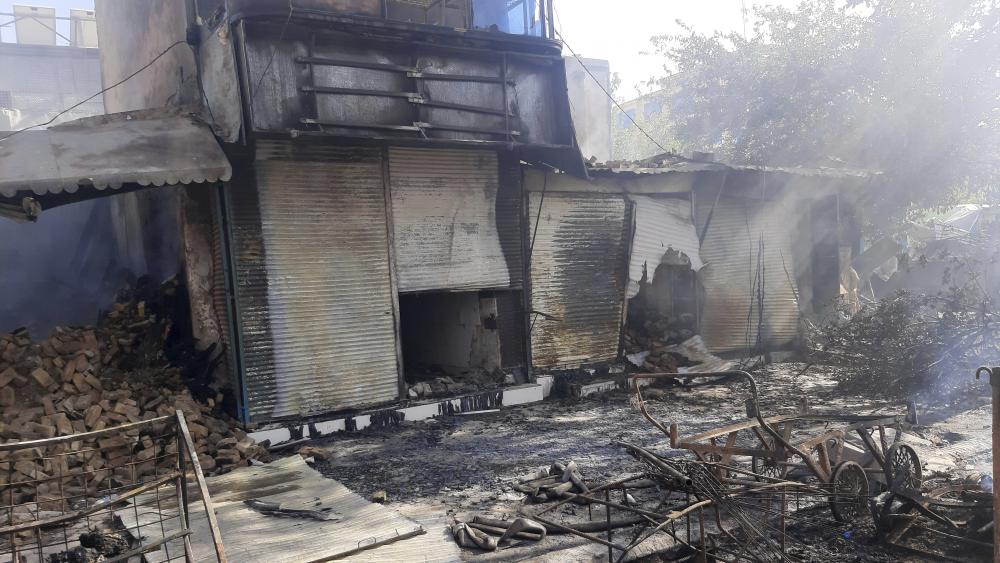 Smoke rises from damaged shops after fighting between Taliban and Afghan security forces in Kunduz city, northern Afghanistan, Sunday, Aug. 8, 2021. (AP Photo/Abdullah Sahil)