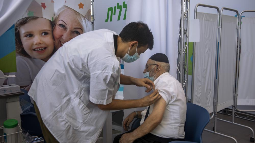 A man receives a third Pfizer-BioNTech COVID-19 vaccine from medical staff at a coronavirus vaccination center in Tel Aviv, Israel, Tuesday, Aug. 10, 2021. Israel is grappling with a surge of infections and urging people over age 60 to get a booster shot.