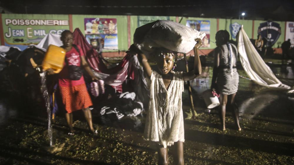 People affected by Saturday's earthquake recover their belongings under the rain of Tropical Depression Grace at a refugee camp in Les Cayes, Haiti, Monday, Aug. 16, 2021. (AP Photo/Joseph Odelyn)