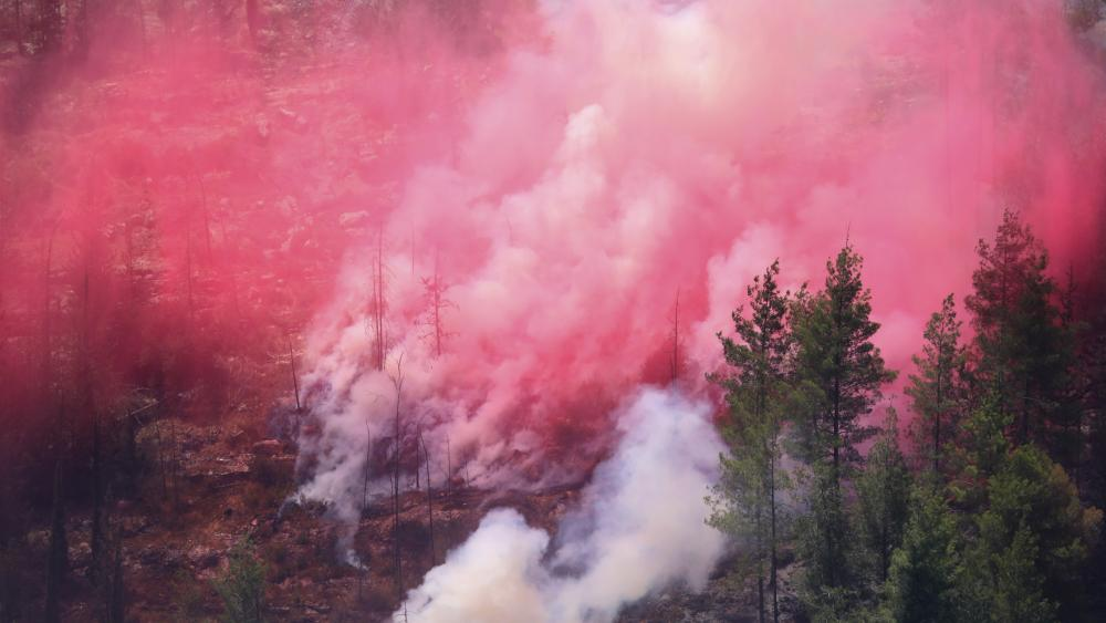 Smoke and red fire retardant sprayed by Israeli firefighting aircraft mingles on a hillside on the third day of wildfires in the Jerusalem mountains, Tuesday, Aug. 17, 2021. (AP Photo/Ariel Schalit)