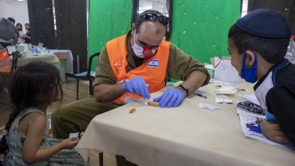An Israeli soldier conducts a COVID-19 antibody test on a child in Hadera, Israel, Monday, Aug. 23, 2021. (AP Photo/Ariel Schalit)