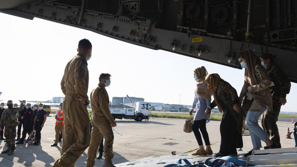 This photo provided by the French Army Thursday, Aug.26, 2021 shows Afghan refugees arriving in a military plane at Roissy airport, north of Paris, Wednesday, Aug.25, 2021. (Eric Cadiou/Etat Major des Armees via AP)