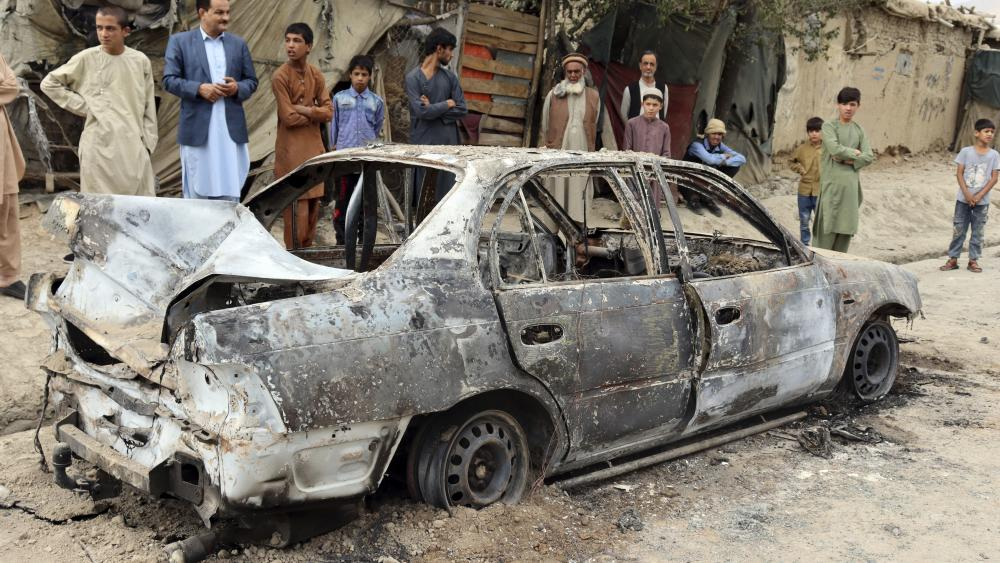 Locals view a vehicle damaged by a rocket attack in Kabul, Afghanistan, Monday, Aug. 30, 2021. (AP Photo/Khwaja Tawfiq Sediqi)