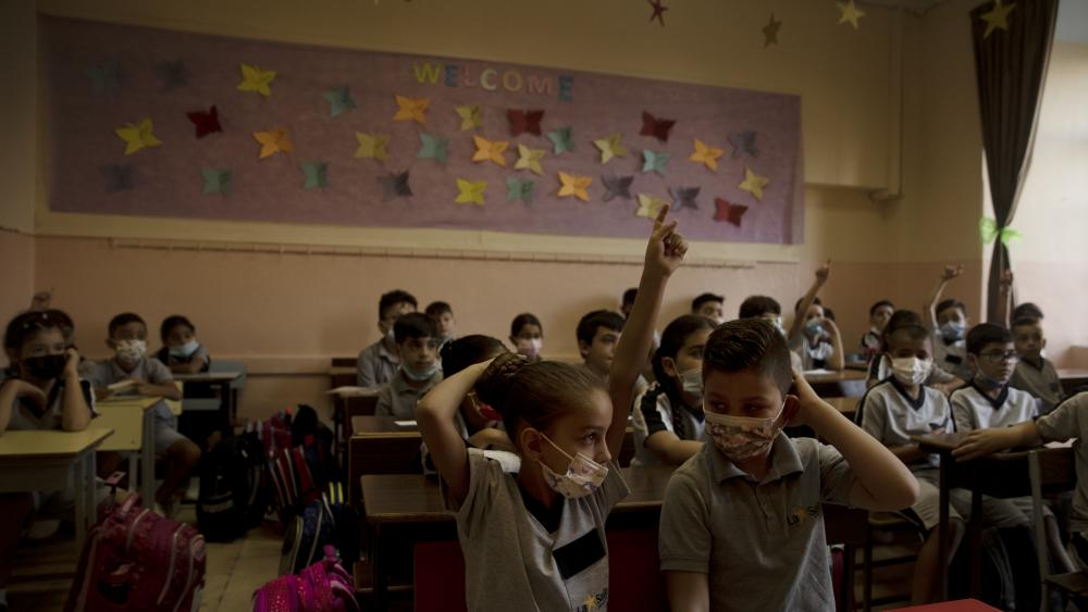 A girl raises her hand in class on the first day of school at College des Freres in the Old City of Jerusalem, Wednesday, Sept. 1, 2021, amid an uptick in coronavirus infections. (AP Photo/Maya Alleruzzo)