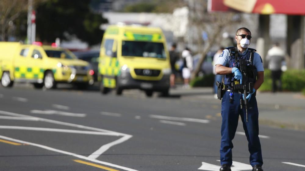A police officer stands outside an Auckland supermarket, Friday, Sept. 3, 2021.(Alex Burton/New Zealand Herald via AP)