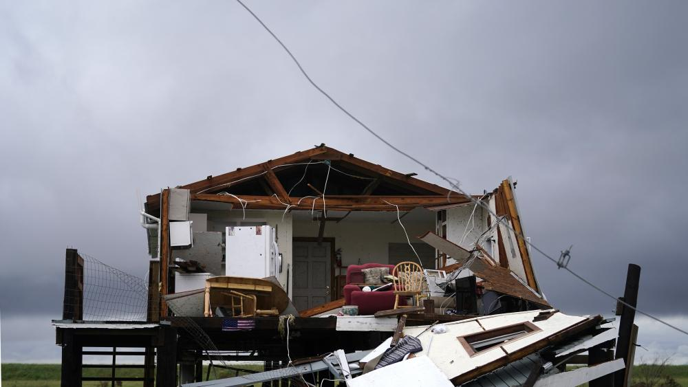 Storm clouds from Tropical Storm Nicholas are seen behind a home that was destroyed by Hurricane Ida, in Pointe-aux-Chenes, La., Tuesday, Sept. 14, 2021. (AP Photo/Gerald Herbert)