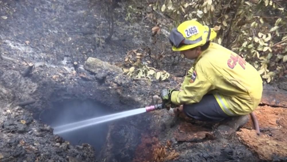 Firefighter putting out a fire in Boulder Creek, California - 26 August 2020. AP video screenshot.