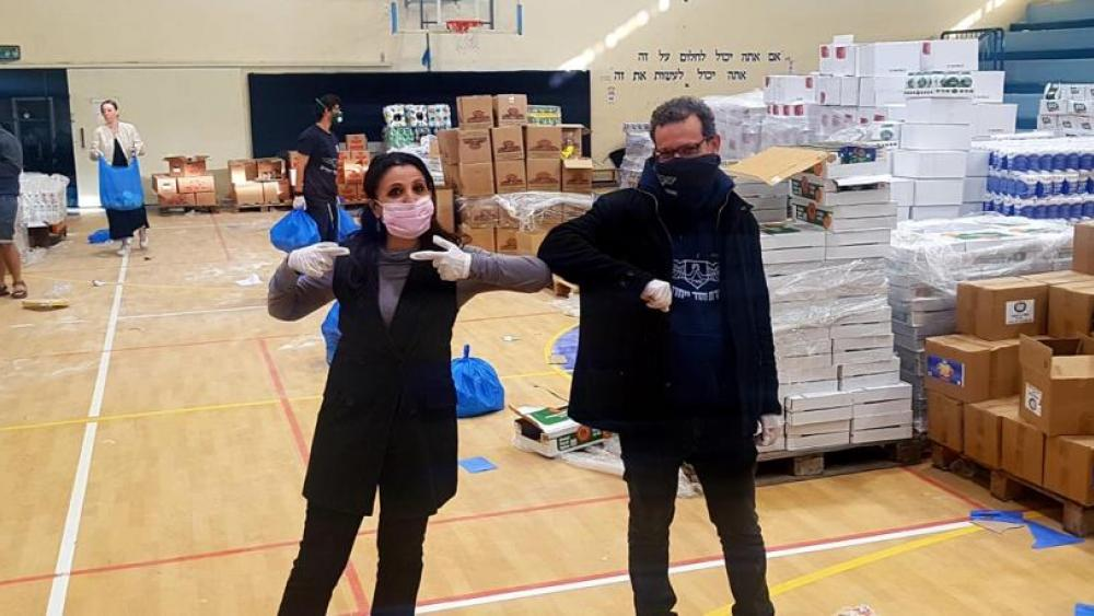 Courtesy: Deputy Mayor Fleur Hassan-Nahoum (L) visits one of the Jerusalem food distribution centers for families in need sponsored by the Genesis 123 Foundation.