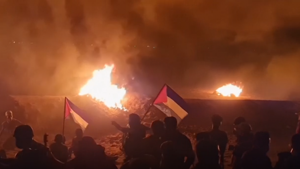Protesters gathering near the border holding Palestinian flags with fires burning. 2 Sept. 2021. Screenshot of AP video.