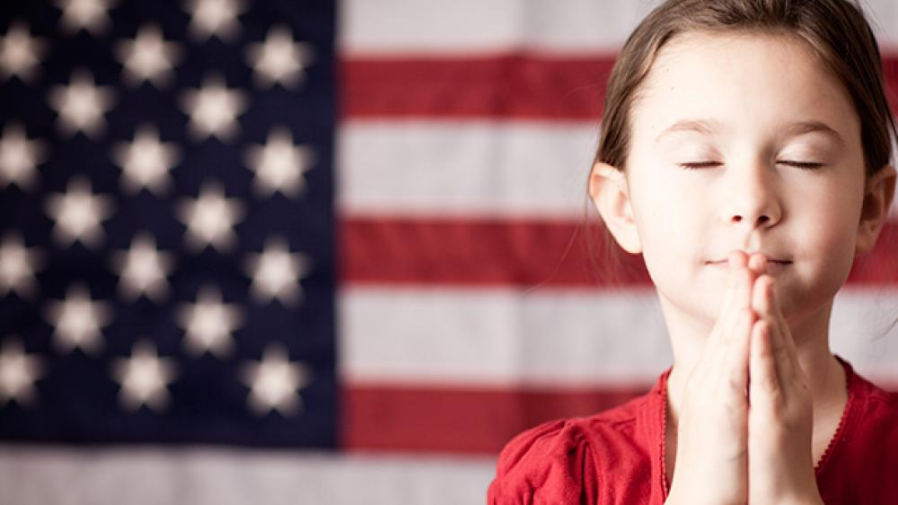 usa flag in the background and little girl praying with eyes closed