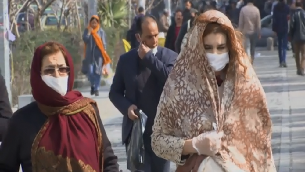 AP footage screenshot: People walking around Iran wearing medical masks