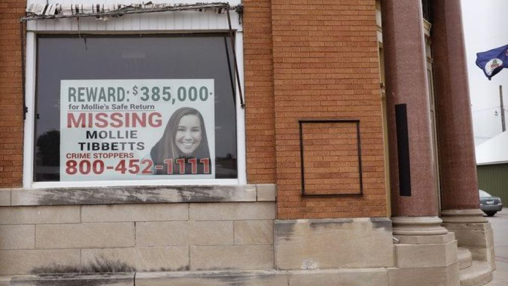 A poster for missing University of Iowa student Mollie Tibbetts hangs in the window of a local business in Brooklyn, Iowa.