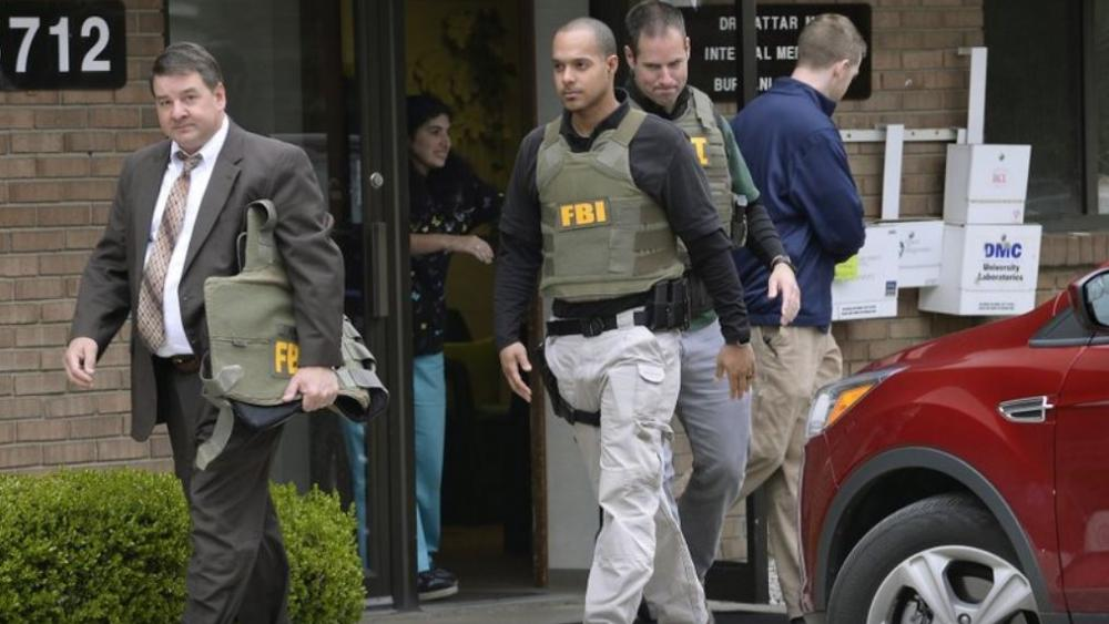 In this April 21, 2017 file photo, FBI agents leave the office of Dr. Fakhruddin Attar at the Burhani Clinic in Livonia, Mich., after completing a search for documents. AP photo.