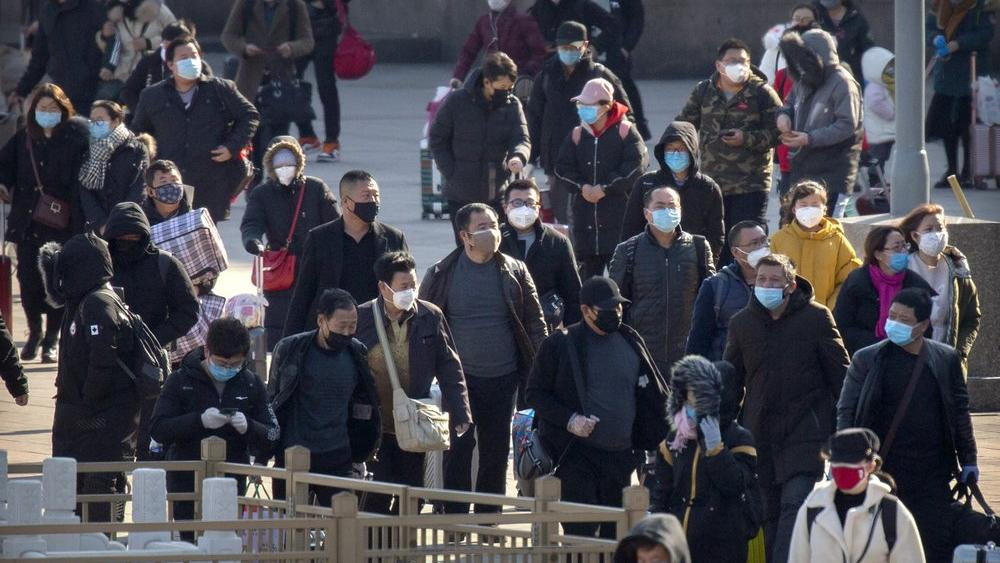 Travelers wear face masks as they walk outside the Beijing Railway Station in Beijing, Saturday, Feb. 15, 2020.