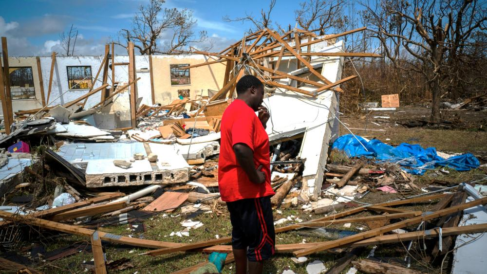 A man cries after discovering his shattered house, not knowing if his 8 relatives who lived there survived Hurricane Dorian on Grand Bahama island (AP Photo/Ramon Espinosa)