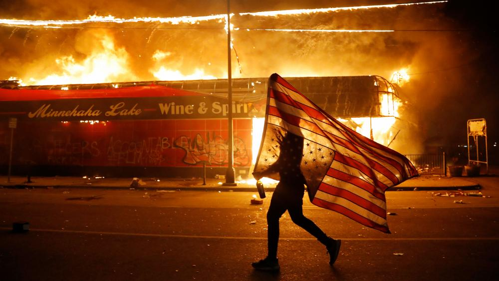 A protester carries a U.S. flag upside down next to a burning building May 28, 2020, in Minneapolis in protests over the death of George Floyd, a black man who died in police custody. (AP Photo/Julio Cortez)