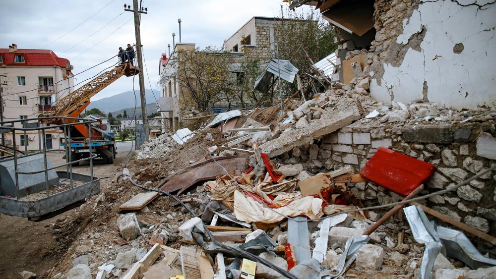 Workers repair communication lines near a house during destroyed by shelling, in Stepanakert, the separatist region of Nagorno-Karabakh, Saturday, Oct. 10, 2020. (AP Photo)
