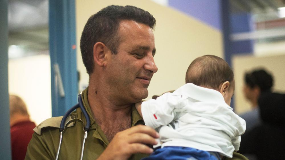 Operation Good Neighbor. Commander comforts a Syrian baby. Photo, IDF