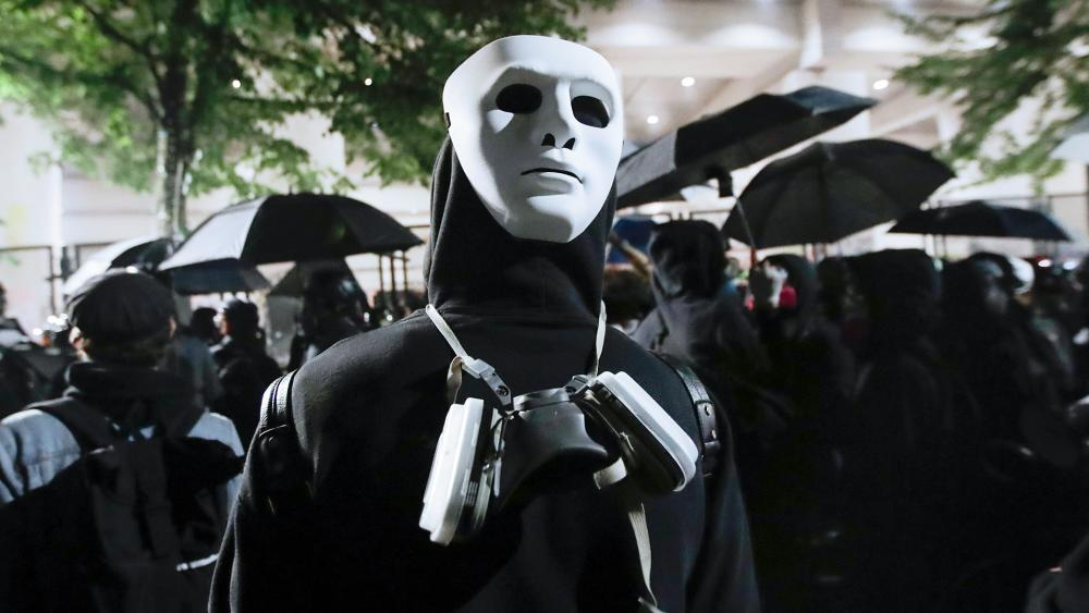 A protester wears a mask during a Black Lives Matter protest at the Mark O. Hatfield US Courthouse in Portland, Ore. (AP Photo/Marcio Jose Sanchez)