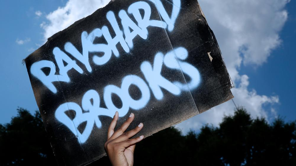 A protester holds up a sign near the Wendy's restaurant where Rayshard Brooks was shot and killed by police Friday evening following a struggle in the restaurant's drive-thru line in Atlanta. (AP Photo/Brynn Anderson)