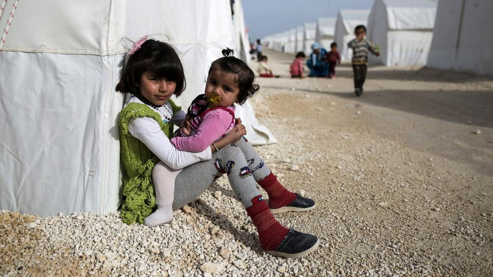 Syrian refugee children who fled violence in Syrian city of Ain al-Arab, known also as Kobani, seen outside their tents in a camp in the border town of Suruc, Turkey, in 2015. (AP Photo)