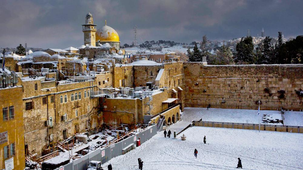 In this Dec. 13, 2013 file photo, the Western Wall, right, and the gilded Dome of the Rock, among the holiest sites for Jews and Muslims, are covered in snow.  (AP Photo/Dusan Vranic, File)