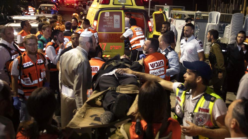 Israeli medics carry wounded ultra-Orthodox men outside a synagogue in Givat Zeev, outside Jerusalem, May 16, 2021. Israeli medics say more than 150 people were injured in the accident. (AP Photo/Sebastian Scheiner)
