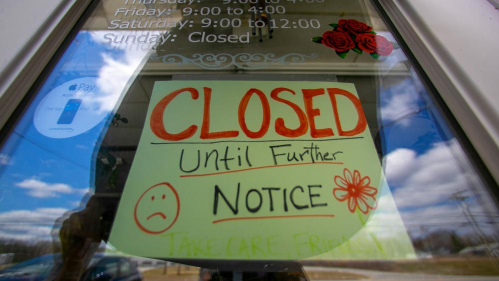 A sign announces a coronavirus closure at a flower shop in Jay, Maine, April 16, 2020. (AP Photo/Robert F. Bukaty)
